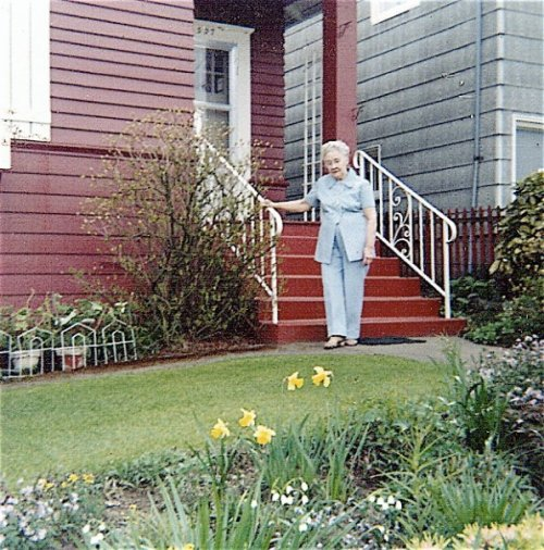 Gram in her springtime garden. I eventually took out this upper patch of lawn and made a path angled across to the left.