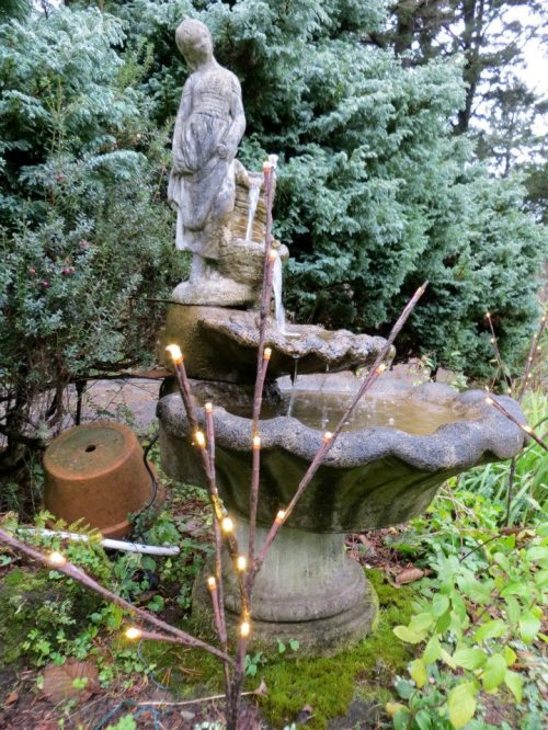 the lady fountain in the lawn bed