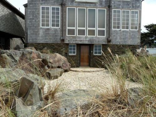 On the next owner is a hardscape I have long admired...swirly rock entry patio, boulders, and beachy grass.