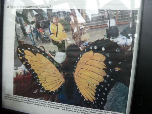 a photo of Sheri in her wings at the Saturday Market booth