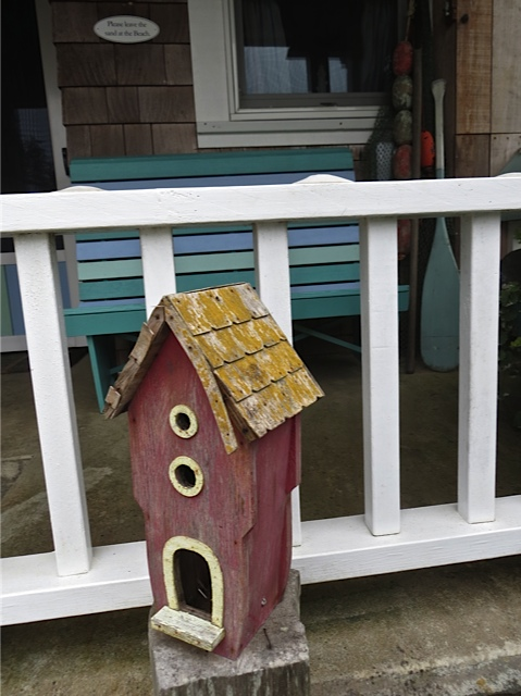 birdhouse by porch rail