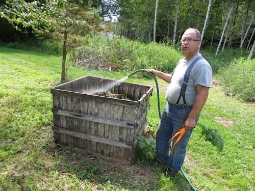 Jim waters down a compost bin.