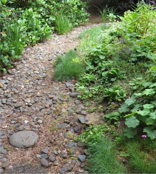 The streambed curves around to the end of the patio.