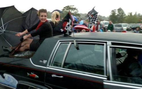 "Jenna's ""hot rod hotties"", riding on the back,  try to slow the car down with brollies."