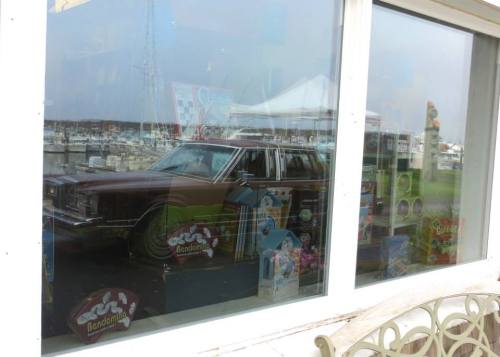 Kelly's son's car reflected in the window of Time Enough Books