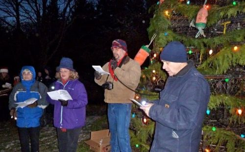 Laurie and Clint Carter join Bruce to lead the caroling.