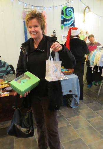 Rebecca, who used to operate The Canoe Room café at the port, shows off her purchases.