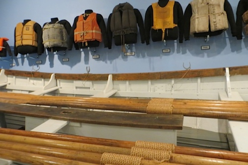 lifejackets hang over an old lifeboat