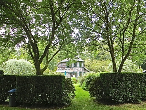 I go through a hedge into a new area (a big lawn with an open sided tent left from an event).  Looking back I can see the house and both silver pears.