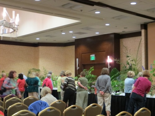 In the lecture hall, participants examine an L shaped display of choice cut flowers and foliage gathered by true plant nuts.