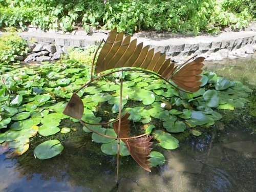 a fish sculpture in the pond