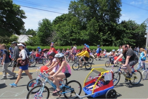 a small town parade with lots of bicycling