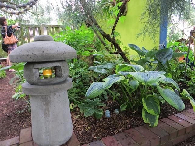 a candle pillar by the shade garden
