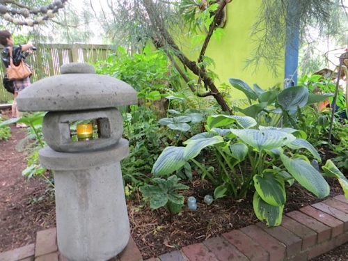a candle pillar by the shade garden