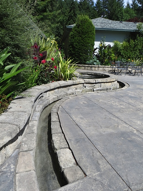 From the round pool, a rill runs across the patio.