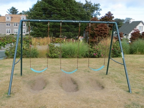 on the lawn after the children went into the cottages, a classic swingset with holes worn by many feet