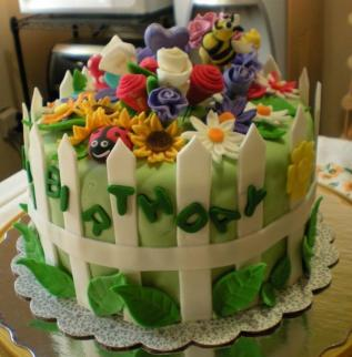 Garden theme birthday cake with white picket fence and ladyug and bee
