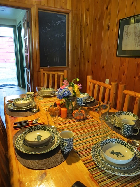 The table, chairs, and beds all have the same rustic wood look.