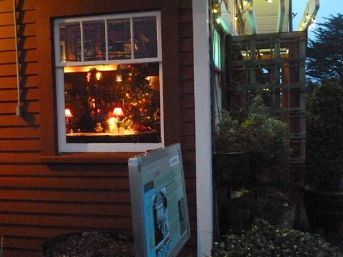 At the Depot, to the right, you can see the window box annuals that still refuse to die, and inside, the lights of the Christmas tree.