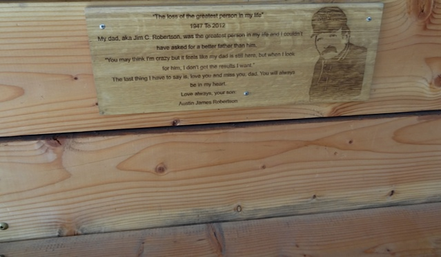 inside the tiny mall, a bench with a touching memorial plaque