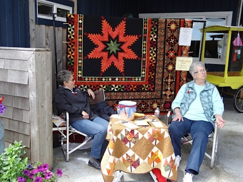 and the Peninsula Quilt Guild raffle booth with this year's prize quilt