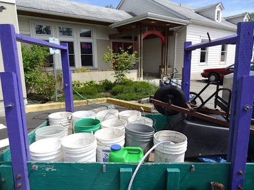 He filled the buckets at the community center so that he could do some watering there, as well.