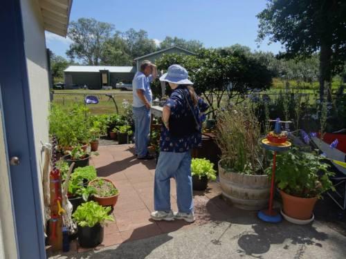 A tour guest in the container veg garden peer into the flower garden.