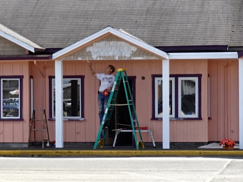 Across the street, building owner Doug paints the trim on the Kabob House restaurant.