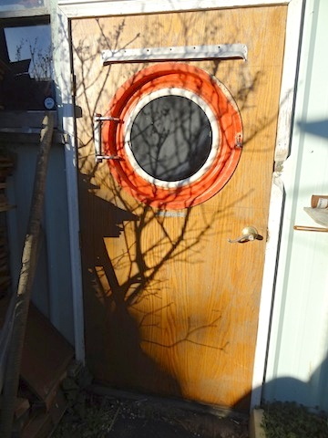 The porthole in this door opens and is made from the door of a front loading clothes dryer!