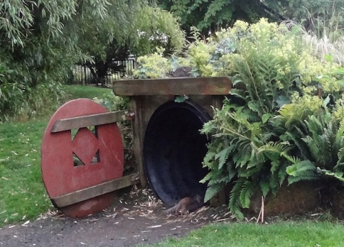 a squirrel running into the hobbit house