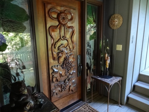 in a breezeway, the door of the house carved by the homeowner