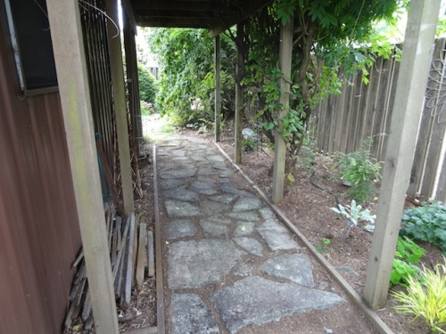 path by a large shed, made of broken concrete, placed well and non trippingly flat.