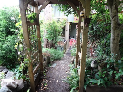 Looking through an arbour to a bridge that goes to the house.