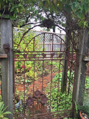 Goodbye to the entry garden with its heart gate and narrow brick path.